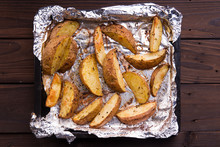 Fried Russet Potato On Tray With Aluminium Foil On Rustic Wooden Background