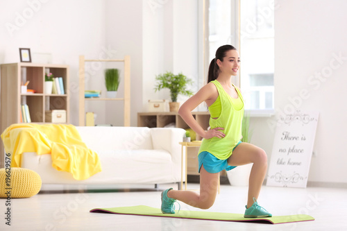 Photo Beautiful young woman doing fitness exercise at home