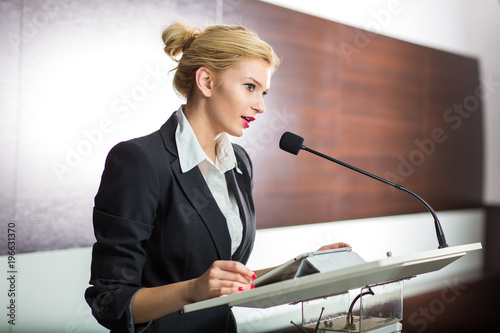 Photo Pretty, young business woman giving a presentation in a conference/meeting setti