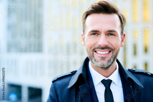 Photographie  Portrait of handsome businessman looking at camera and smiling outdoors