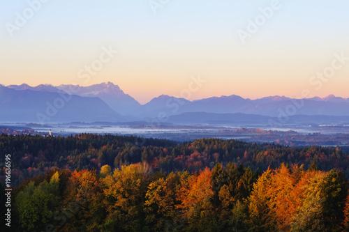Germany, Bavaria, Upper Bavaria, Alpine foothills, Church tower of Koenigsdorf, Zugspitze and Ammergau Alps at sunrise, View from Peretshofener Hoehe in autumn