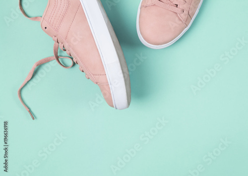 Fotografia  Fashion pink sneakers on the pastel green background.