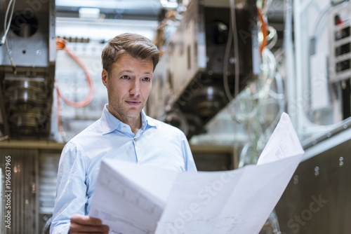 Businessman in factory holding plan