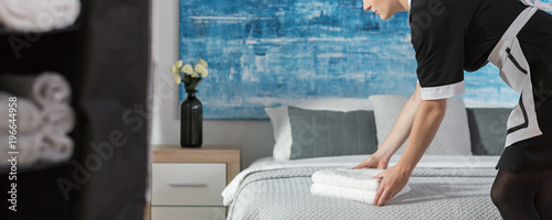 Maidservant arranging towels on bed