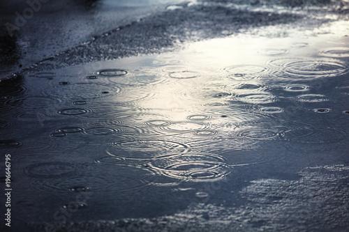 rain puddles on a pavement in city Fototapeta