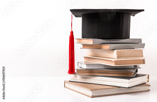 Photo Square academic hat on stack of different books isolated on white