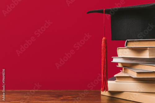 Fotografia  Cropped view of stack of books with academic cap on red