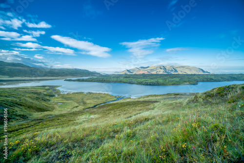 Fotobehang Olijf Landscape photography of a mountain in Iceland having smooth running river in foreground with green autumn grass meadow