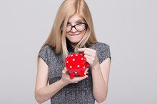 Young Excited Blonde Woman Put One Euro Into Piggy Bank