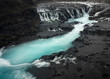 Icelandic Icy Blue River, surrounded by Black Rock along Golden Circle in Winter