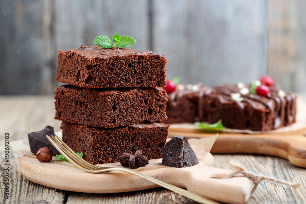 Fototapeta Chocolate brownie cake, dessert with nuts on wooden background.