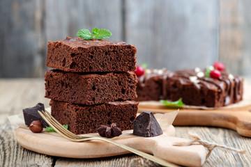 Čokoladni brownie kolač, desert s orasima na drvenoj podlozi.