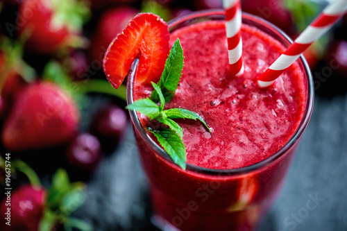 Fototapeta Glass with two straws filled with strawberry smoothie on black with strawberries. obraz