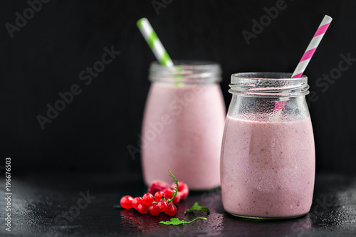 Foto op Aluminium Milkshake Two glasses with berry pink smoothies with currant and cranberry, selective focus