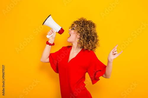 Fotografía  Attractive woman with curly hair with loudspeaker