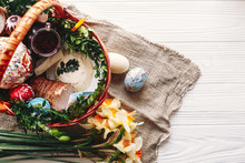 Stylish Basket With Painted Eggs, Bread, Ham,beets, Butter On Rustic Wood Background With Spring Flowers And Candle, Top View. Easter Food For Blessing In Church. Happy Easter Concept