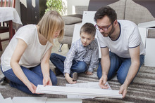 Mama Tata I Synek Samodzielnie Składają Meble. Siedzą Na Dywanie I Porównują Element Mebla Z Ilustracją, Która Znajduje Się W Instrukcji Montażu
