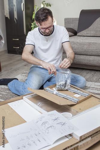 Fotografie, Tablou  Mężczyzna klęczy na dywanie nad kartonem z elementami mebli do samodzielnego montażu i rozcina nożyczkami torebkę foliową z wkrętami i śrubami do montażu
