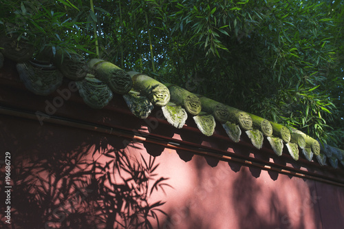 Sun light on Chinese style red wall with bamboo around