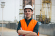 Young man in construction in orange vest and helmets