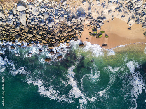 Waves crashing on rocky beach - view from above