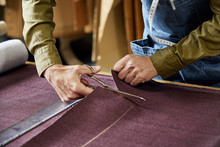 Worker Cutting Fabric With Scissors In Sofa Workshop