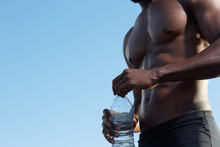 Close Up Portrait Of African Black Sportsman On Topless Holding A Water Bottle