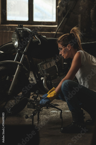 Deurstickers Retro Young female working on restoration of old /vintage motorbikes in old rusty motorbike garage/workshop