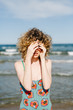 Young woman covering face on beach