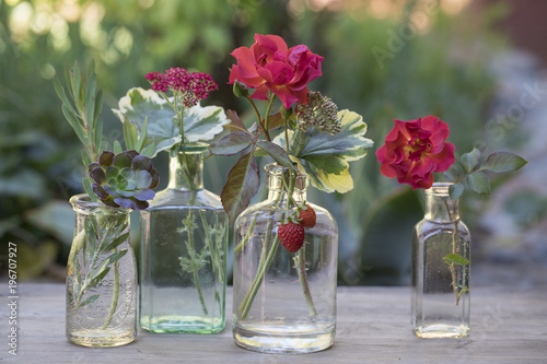 Close-up of small flowers in glass jars