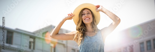 fototapeta na drzwi i meble Composite image of portrait of a woman touching her straw hat
