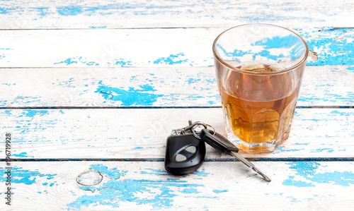 Fotografía  A glass of whiskey and car keys on on the old blue table.