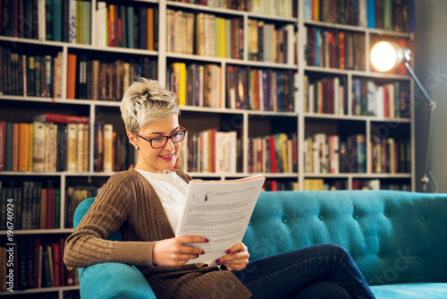 Fotografija  Charming beautiful satisfied middle age short hair woman sitting on the sofa in the library and analysis students tests or business management