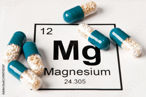 Photo  pills with mineral Mg (magnesium) on a white background with an inscription from