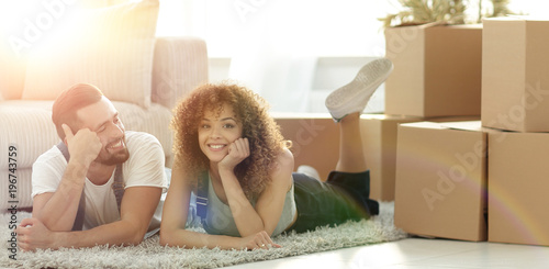 Photo concept of moving to a new home. Happy couple lying on the floor