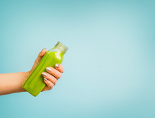 Female Hand Holding Bottle With Green Summer Beverage: Smoothie Or Juice At Blue Background.