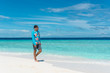 Man walking on beach with transparent water of ocean in Maldives