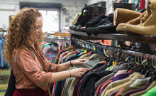 Woman Browsing Through Vintage Clothing In A Thrift Store.