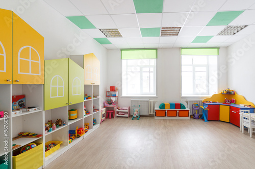 Valokuva  Spacious white game room in the kindergarten with toys, two large windows and tables for classes