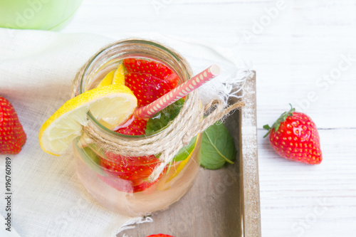 Foto op Canvas Restaurant Mineral water with fresh strawberries, lemon and mint in jar on a white wooden background, copy space