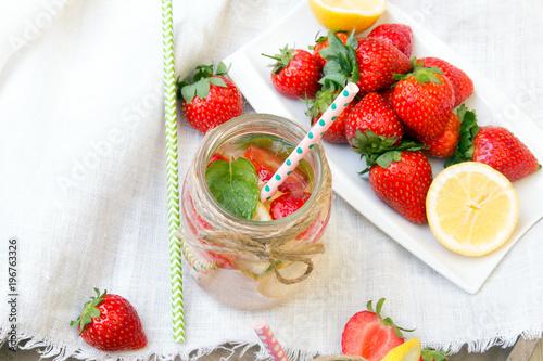 In de dag Opspattend water Mineral water with fresh strawberries, lemon and mint in jar on a white wooden background, copy space