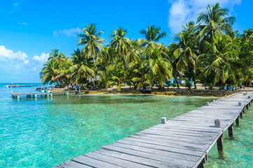 Fototapeta Tobacco Caye - Relaxing on Wooden Pier on small tropical island at Barrier Reef with paradise beach, Caribbean Sea, Belize, Central America