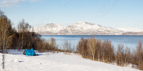 Fotobehang Lichtblauw Blue tent on a snowy field in the polar area with a view on a fjord and mountains covered in snow near Tromsø Norway