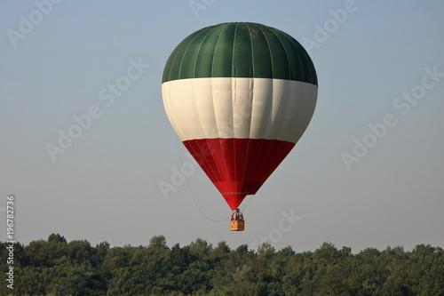 Fototapeta Balon na rozgrzane powietrze, w pasy zielony, biały i czerwony, w powietrzu, ponad drzewami obraz