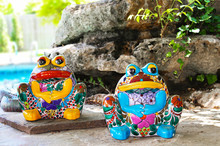 Two Brightly Colored And Decorated Ceramic Frogs Sit By Landscaping Rocks By Swimming Pool