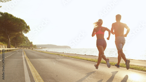 Poster Jogging COPY SPACE: Athletic young couple jogging near the sea on perfect day in summer