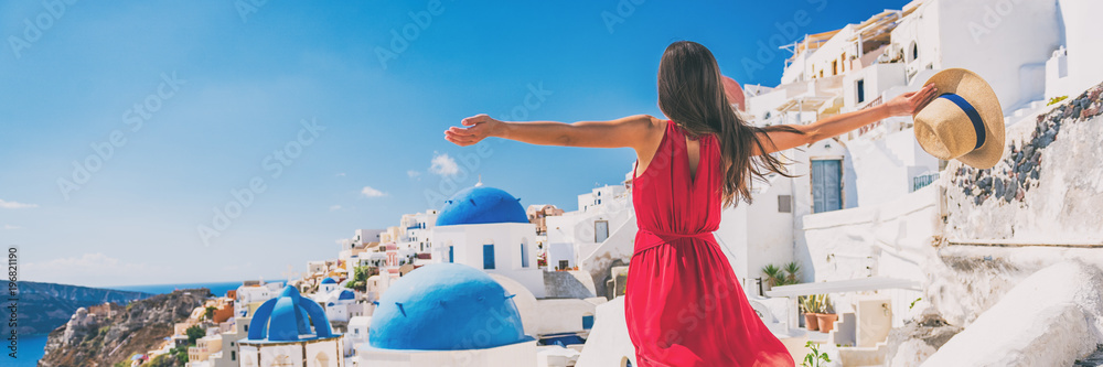 Fototapeta Europe travel vacation fun summer woman feeling free dancing with arms open in freedom at Oia, Santorini, Greece island. Carefree girl tourist banner panorama.