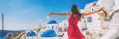 Fototapeta Europe travel vacation fun summer woman feeling free dancing with arms open in freedom at Oia, Santorini, Greece island. Carefree girl tourist banner panorama. obraz
