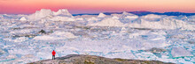 Greenland Travel Hiker Tourist Man Trekking At Sunset. Adventure Expedition In The Arctic Ocean, Ice Floating From Icebergs In Ocean. Banner Panorama.