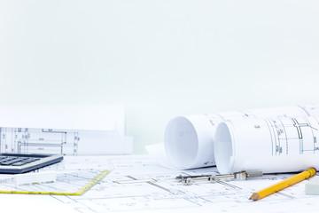 technical project plan, blueprint rolls, pencil, compass, calculator on architect desk. construction background.